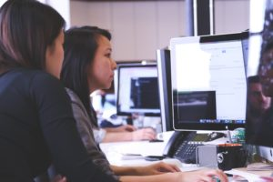 Female Marketers working at an Apple computer screen in a Digital Marketing Agency, Essex