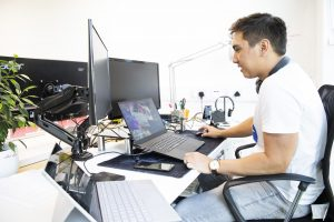 man in ventura digital office sat at computer and laptop with plant